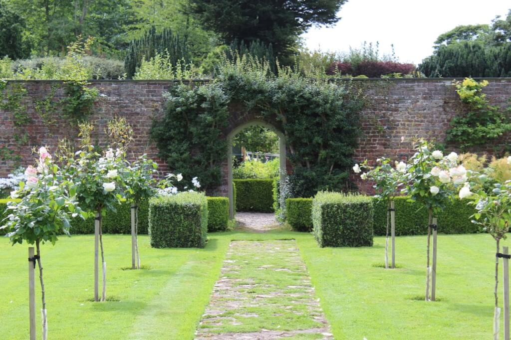 A formal garden gate with clipped hedges and topiary