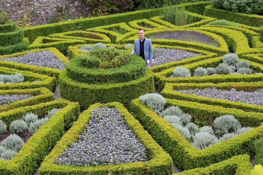 Lee Burkhill Award Winning Garden Designer standing in a topiary maze