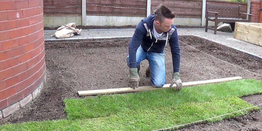 Garden Ninja unrolling turf on a garden makeover