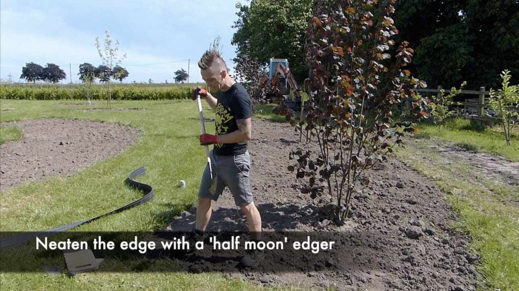 Edging a lawn with a half moon edger tool