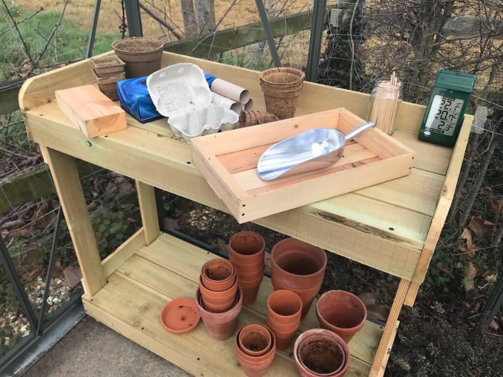 A wooden seed bench full of pots garden ninja