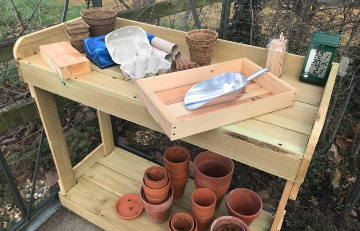 A wooden seed bench full of pots garden ninja