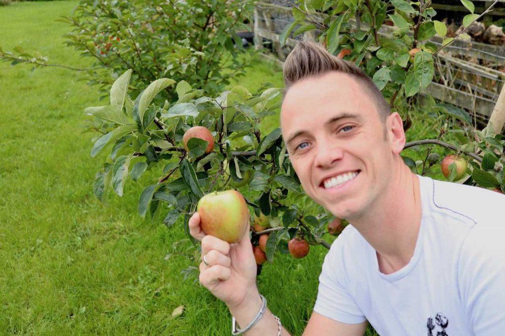 Garden Ninja smiling holding an apple