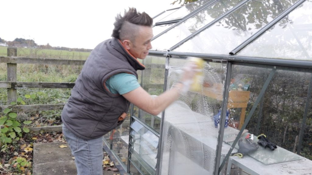 Garden Ninja washing the outside of a greenhouse